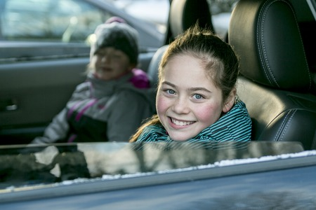 winter: A caucasian girl in warm clothes traveling in a car seat Stock Photo
