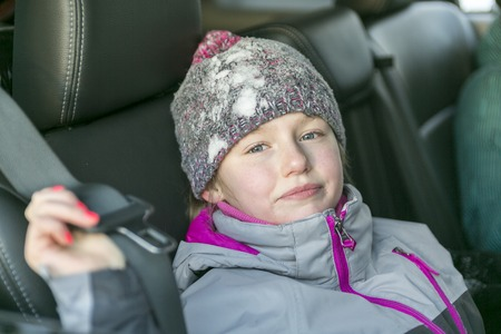 warm clothes: A caucasian girl in warm clothes traveling in a car seat Stock Photo