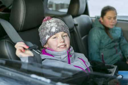 safeness: A caucasian girl in warm clothes traveling in a car seat Stock Photo