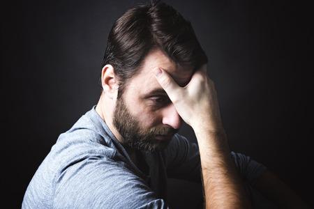 Ein Porträt des Mannes sitzt in Dunkelheit und nachdenklich