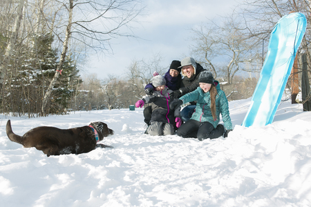 dog sled: Two Happy parents and their kids in winterwear