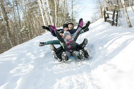 Twee kinderen met de ouders wordt sleeën in de winter-landschap