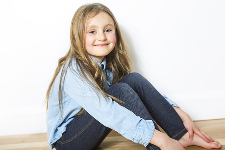 teen feet: closeup image of a pretty little girl sitting on the floor in jeans