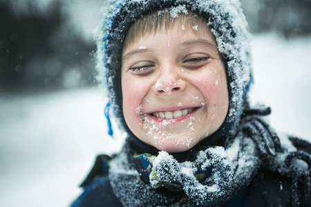 Een kleine jongen spelen met sneeuw buiten in de winter