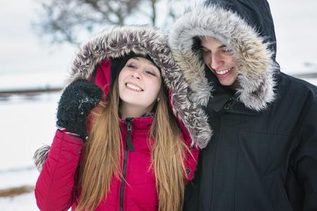 teen love: Two nice teenagers havinf fun on the snow field Stock Photo
