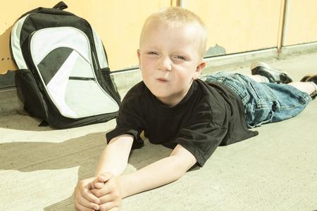 非常に悲しい少年は、学校の校庭でのいじめに地面の縫い目に横たわっていた。 写真素材 - 52523870