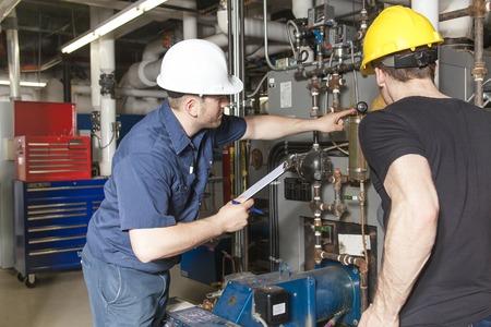 ingenieria industrial: Dos repairmans ingeniero o inspector que revise el sistema.