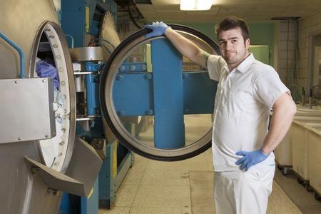 Een industriële wasmachines met een werknemer.