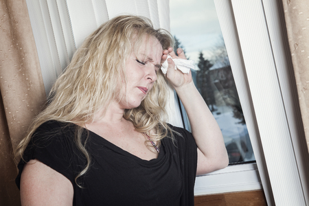 depress: A woman close to a window feel depress.