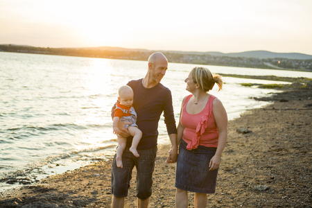 three person: A Family of three person is standing on sunset and sea backdrop Stock Photo