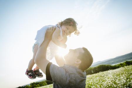 iluminado a contraluz: Un padre alegre feliz con la hija en la puesta del sol