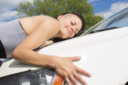 female driver: A Cheerful young female driver hugging her new car Stock Photo