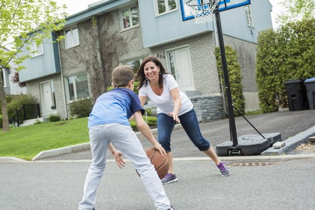 mum and child: A Happy family having fun outside with a basketball.