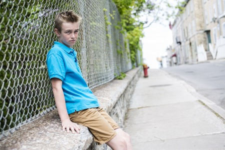 juvenile delinquent: A young teen boy looking out of a fence