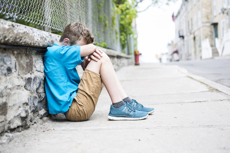 A Photo of Sad and Stressed Kid sit by the Wall outdoor Stock Photo