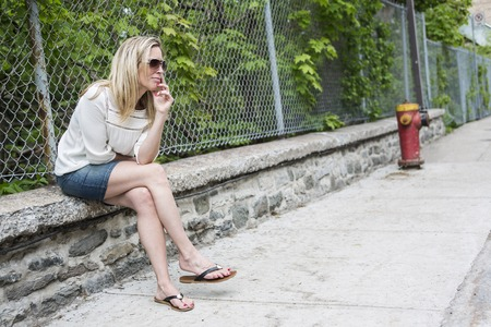 30 to 40 year old: Woman Outdoors with sunglasses sit on a fence Stock Photo