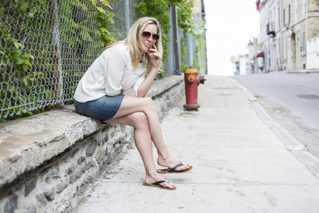 40 year old woman: Woman Outdoors with sunglasses sit on a fence Stock Photo