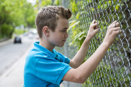 detained: A young teen boy looking out of a fence