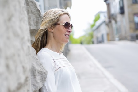 Woman Outdoors with sunglasses beside a building