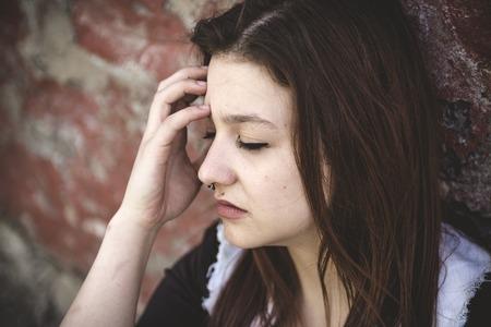 Una ragazza triste con il fronte motional mattoni sfondo