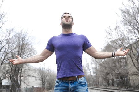 A man standing with arms raised outdoors. Concept about freedom, faith and celebration.