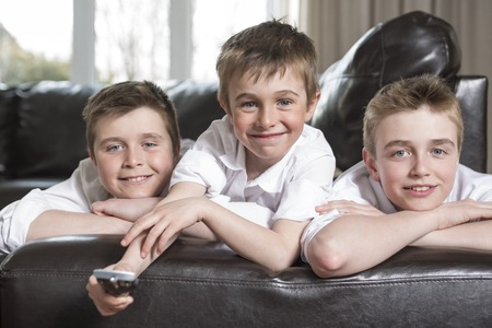 brothers: Three brothers hugging and playing on the sofa Stock Photo