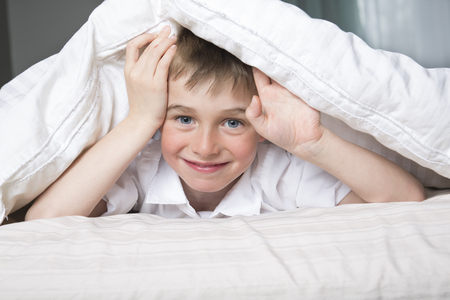 coverlet: A Smiling boy hiding in bed under a white blanket or coverlet. Stock Photo