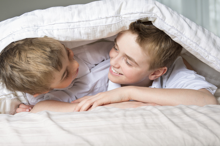 coverlet: two boys hiding in bed under a white blanket or coverlet.
