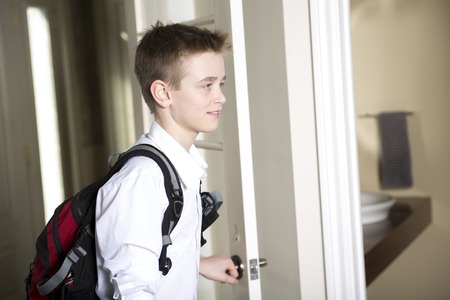 coming home: a teen coming home passing through the door. Stock Photo