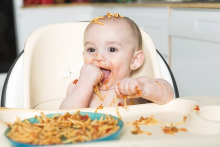 mess: A Little b eating her dinner and making a mess Stock Photo