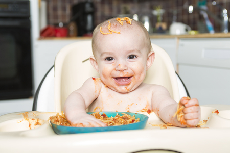 A Little b eating her dinner and making a mess Foto de archivo
