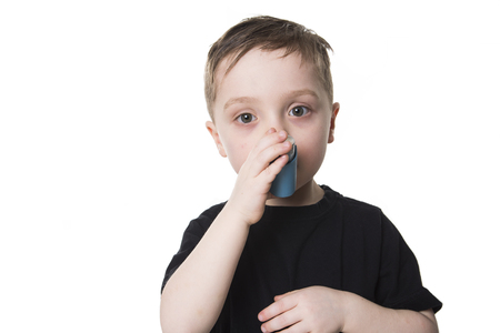 4 years old: A Boy 4 years old inhales himself on a white background