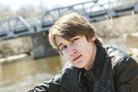 A teen sits outside close to a bridge Leather jacket.