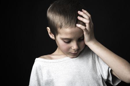 A stressed sad boy on studio bad time Stock Photo