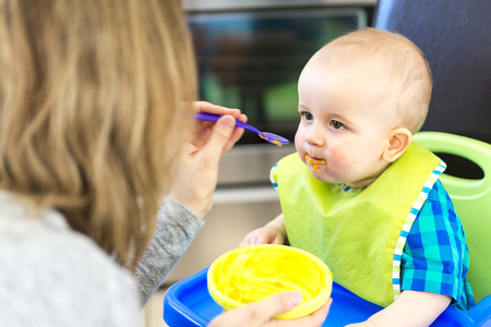 highchair: A Mother feeding hungry baby in the highchair indoors