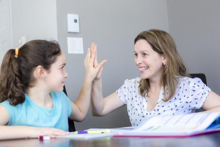 Eine Reife Mutter ihr Kind bei den Hausaufgaben zu Hause zu helfen. Standard-Bild