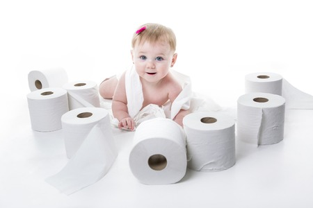 スタジオの白バック グラウンドでトイレット ペーパーを裂く幼児