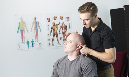 myofascial: A Chiropractor male exercising therapy at office