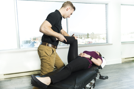 osteopath: A Male Osteopath Treating Female Patient With Hip Problem Stock Photo