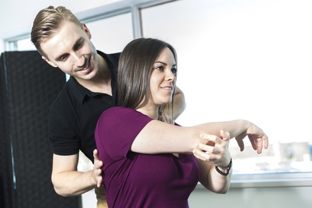 A Doctor examining his patient arm in medical office