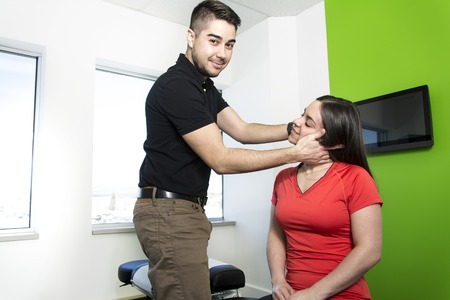 A woman sitting while being massaged by a man in a room Stock Photo