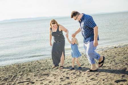 familial affection: A Family of three on beach having fun together