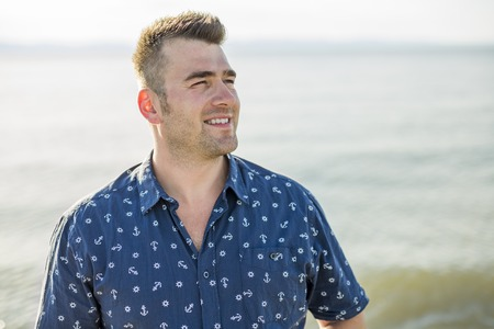 mid adult: A Portrait of mid adult man in blue shirt side beach