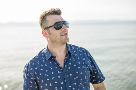 A Portrait of mid adult man in blue shirt side beach