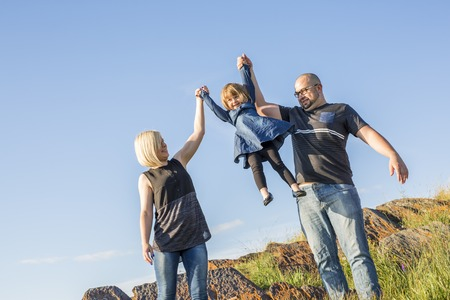 familial affection: A Family of three close to a beach having fun together