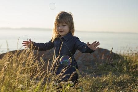 A Cute little girl standing close to beach at sunset