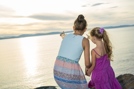 fraternal: two sisters family at the beach on sunset having fun Stock Photo
