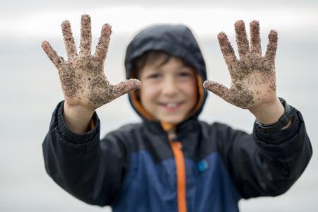 beach rain: A boy enjoying the rain and having fun outside on the beach on a gray rainy Stock Photo