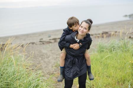 beach rain: Family two enjoying the rain and having fun outside on the beach on a gray rainy