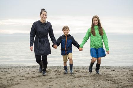 beach rain: Family of three enjoying the rain and having fun outside on the beach on a gray rainy